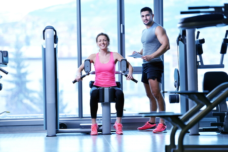 Gym woman exercising with her personal trainer photo