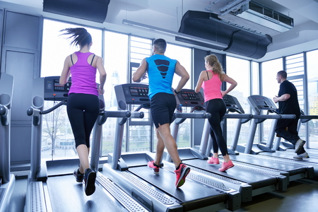 gym girl: group of young people running on treadmills in modern sport  gym
