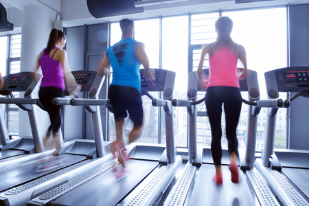 group of young people running on treadmills in modern sport  gym photo
