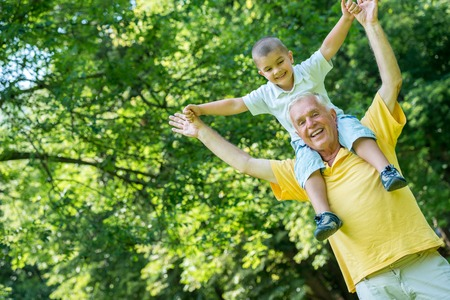 fit ball: happy grandfather and child have fun and play in park on beautiful  sunny day