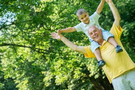 grandfather grandson: happy grandfather and child have fun and play in park on beautiful  sunny day