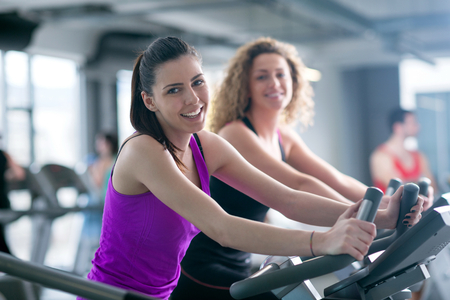 treadmill: group of young people running on treadmills in modern sport  gym