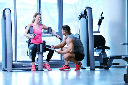 fitness trainer: Gym woman exercising with her personal trainer