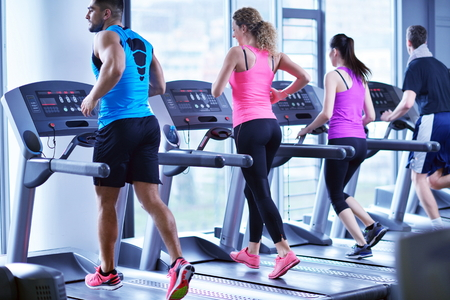 cardio fitness: group of young people running on treadmills in modern sport  gym