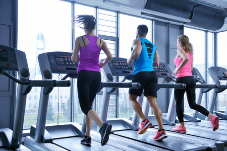 gym: group of young people running on treadmills in modern sport  gym