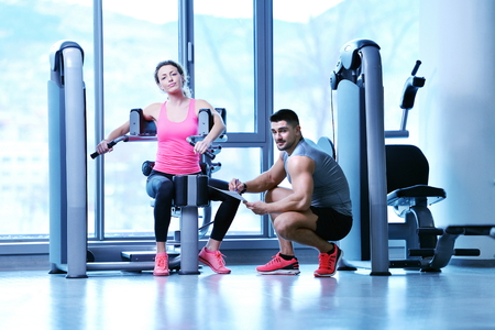 'personal beauty': Gym woman exercising with her personal trainer