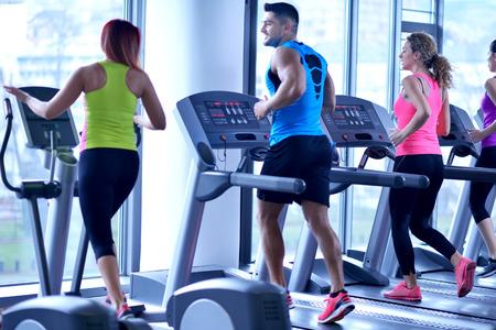 Grupa młodych ludzi działających na bieżnie w nowoczesnej siłowni sportu