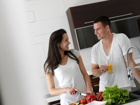 vegetables young couple: happy young couple have fun in modern kitchen indoor while preparing fresh fruits and vegetables food salad