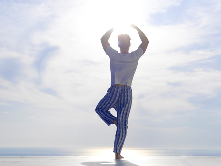 handsome young man practicing yoga on in modern home terace with ocean and sunset in background photo