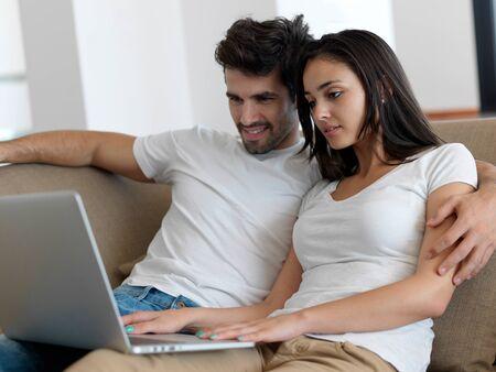 pagando: feliz pareja relajada joven que trabaja en la computadora portátil en casa moderna de interior