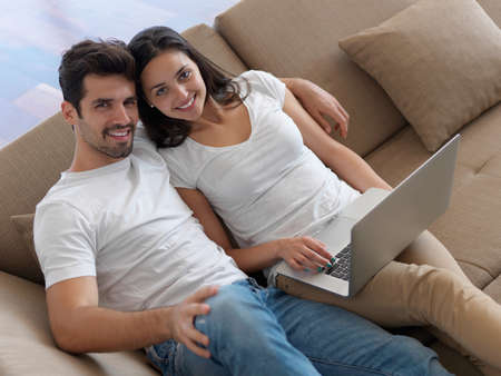 couple on couch: happy young relaxed  couple working on laptop computer at modern home indoor Stock Photo