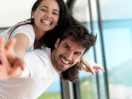 ロマンチックな幸せな若いカップルは、屋内で近代的な家でリラックスし、楽しみを持っています