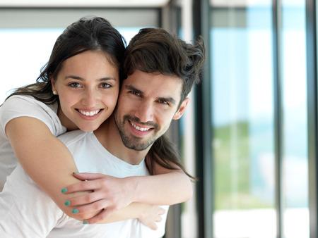 ロマンチックな幸せな若いカップル室内の現代家でリラックスして楽しい時を過す