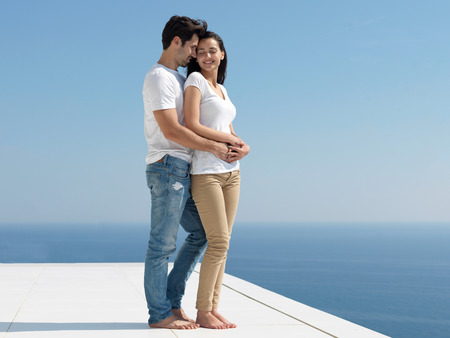 family portrait: happy young romantic couple have fun relax smile at modern home outdoor terace balcony terace