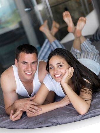 happy young couple relax and have fun in bed photo