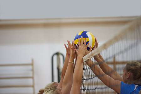volleyball game sport with group of young beautiful girls indoor in sport arena school gym Stock Photo