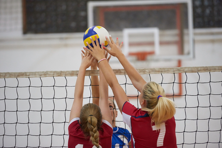 volleyball game sport with group of young beautiful girls indoor in sport arena school gym Imagens