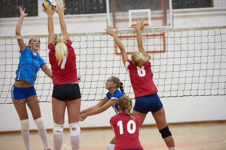 volleyball game sport with group of young beautiful girls indoor in sport arena school gym Foto de archivo