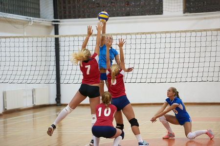 volleyball game sport with group of young beautiful girls indoor in sport arena school gym Standard-Bild