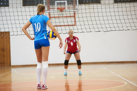 school gym: volleyball game sport with group of young beautiful girls indoor in sport arena school gym Stock Photo