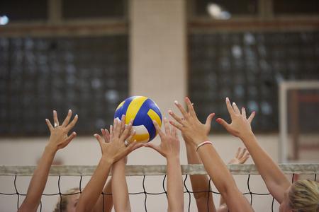 pelota de voley: deporte juego de voleibol con grupo de hermosas muchachas interiores en el deporte gimnasio de la escuela arena
