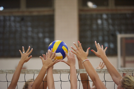 Juego de voleibol deportivo con un grupo de chicas jóvenes y hermosas de interior en el gimnasio de la escuela de arena deportiva