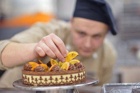 Closeup of a concentrated male pastry chef decorating dessert cake food in the kitchen photo