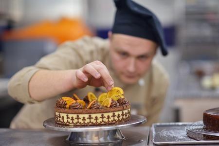 decoracion de pasteles: Primer plano de una decoración de pasteles cocinero de sexo masculino alimentos pastel postre concentrado en la cocina Foto de archivo