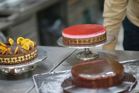 decoracion de pasteles: Primer plano de un chef de repostería masculina concentrado decoración de pastel de postre en la cocina