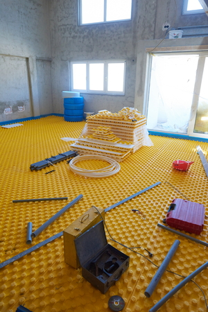 posed: yellow underfloor heating posed in a under construction building