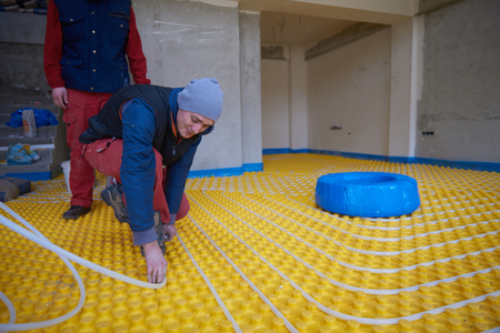 conduction: Group of workera installing underfloor heating and colling in modern home