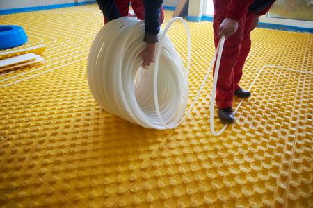 conduction: group of worker installing underfloor heating  in modern home