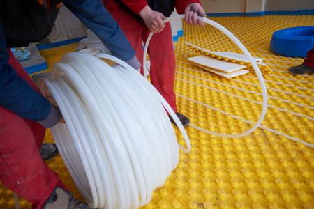 convection: group of worker installing underfloor heating  in modern home