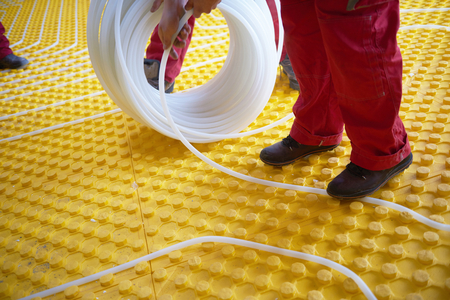 conduction: grouo of workera installing underfloor heating and colling in modern home Stock Photo