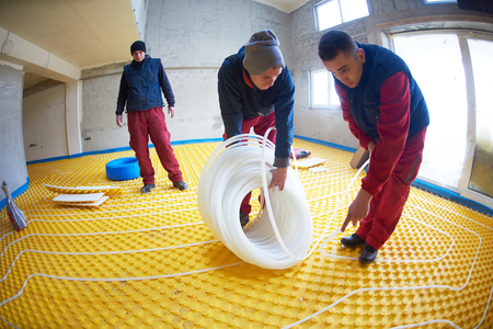 Group of worker installing underfloor heating and colling in modern home photo