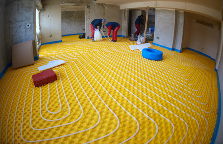 convection: Group of worker installing underfloor heating and colling in modern home Stock Photo