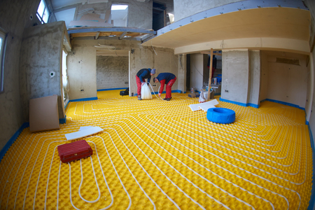 grouo of workera installing underfloor heating and colling in modern home photo