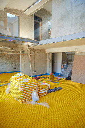 heat home: yellow underfloor heating posed in a under construction building