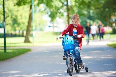 family in park: Young boy on the bicycle at Park Stock Photo
