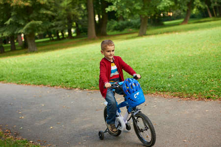 family activities: Young boy on the bicycle at Park Stock Photo