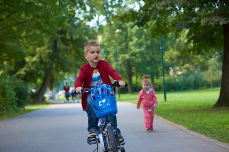 family in park: happy kids in park, boy and girl in nature with bicycle have fun