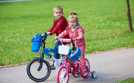 happy kids in park, boy and girl in nature with bicycle have fun photo