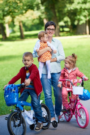 happy family playing together outdoor  in park mother with kids  running on grass photo