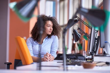 looking at computer: happy young curly  business woman in the modern office Stock Photo