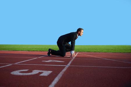 육상 경주 트랙에서 실행할 준비와 스프린트 시작 위치에서 비즈니스 남자 스톡 콘텐츠