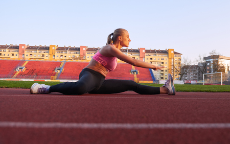 woman stretching: young runner sporty woman relaxing and stretching on athletic race track Stock Photo