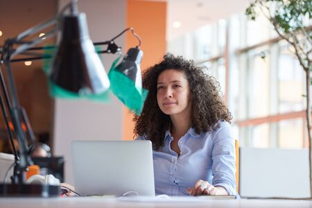 person computer: happy young curly  business woman in the modern office Stock Photo
