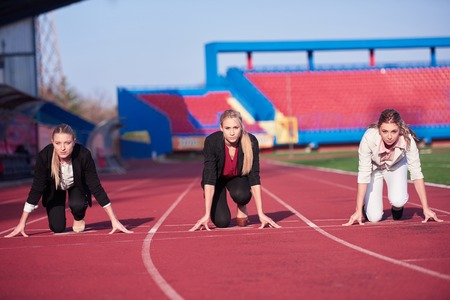 sprint: business woman in start position ready to run and sprint on athletics racing track Stock Photo
