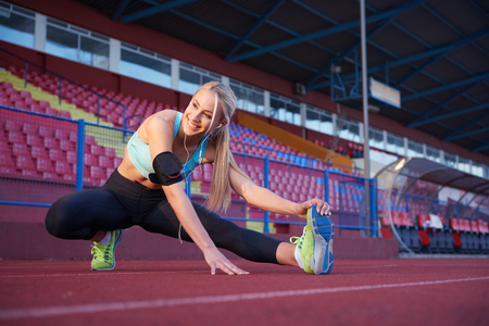 stretch: young runner sporty woman relaxing and stretching on athletic race track Stock Photo