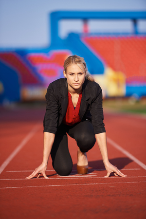 competing: business woman in start position ready to run and sprint on athletics racing track Stock Photo